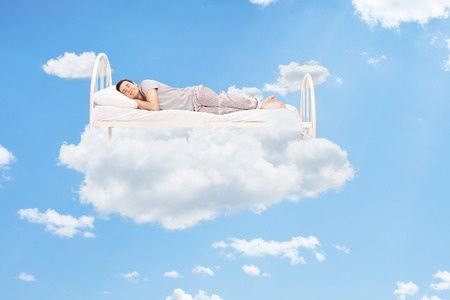 37120773 - man sleeping on a bed in the clouds high up in the sky